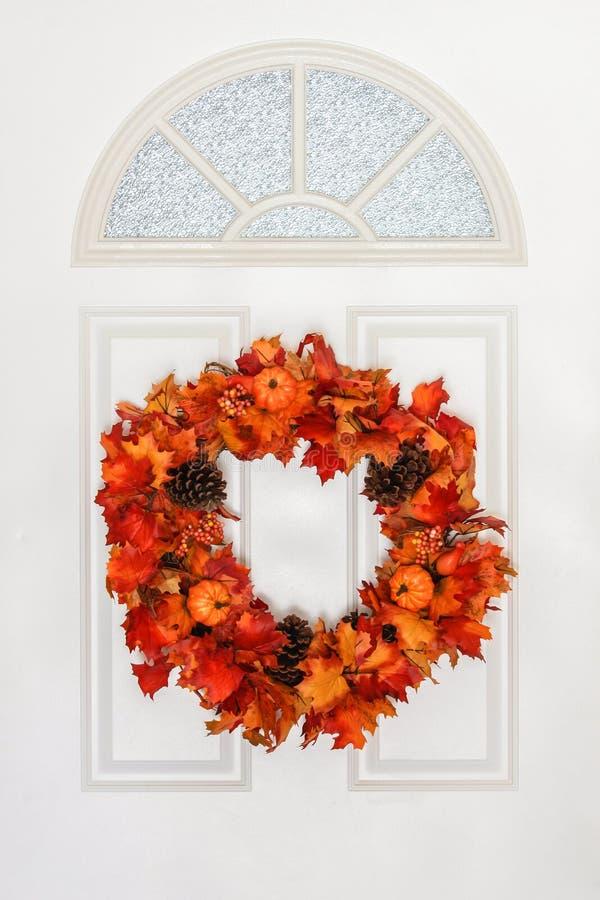垂悬在白色门的秋天花圈 库存图片