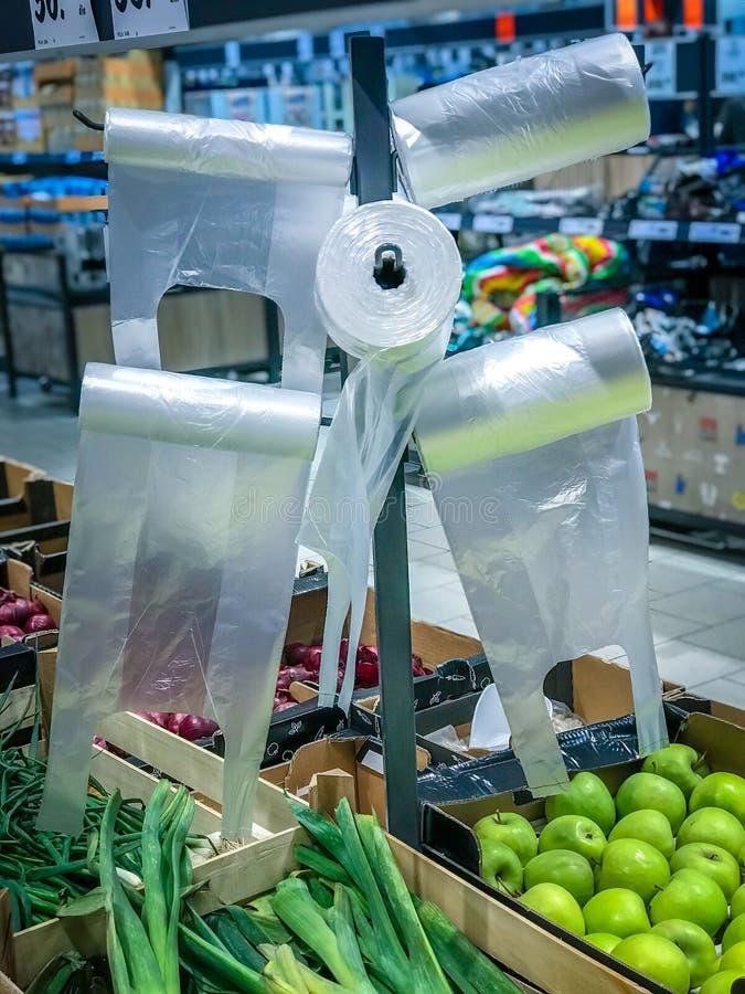 垂悬在立场的塑料玻璃纸袋子在超级市场 免版税库存图片