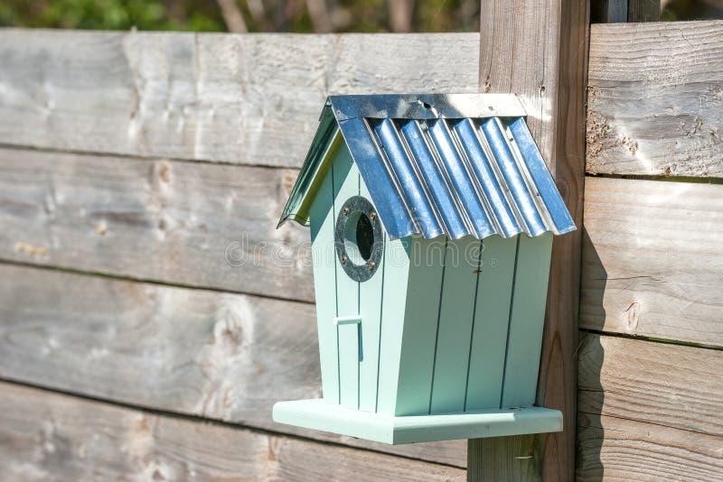 垂悬在篱芭的逗人喜爱的鸟舍 库存照片