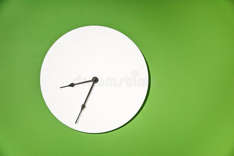垂悬在纯净的草绿色墙壁上的经典壁钟 免版税库存照片