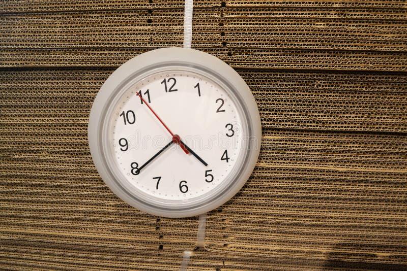 垂悬在纸盒箱子的壁钟 库存照片