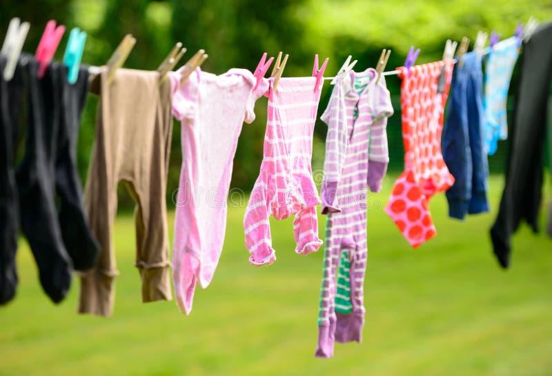 垂悬在线的衣裳在庭院里 免版税库存图片
