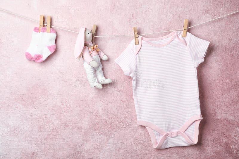 垂悬在绳索的婴孩衣裳和玩具 免版税库存图片