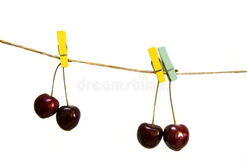 垂悬在绳索的晒衣夹的樱桃 库存图片