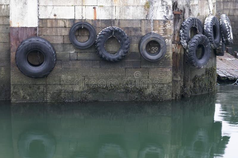 垂悬在绳索的汽车轮胎对港口墙壁在港船坞保护船和小船 库存照片