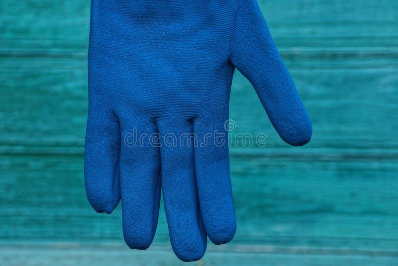 垂悬在绿色背景的新的蓝色工作手套 免版税库存图片