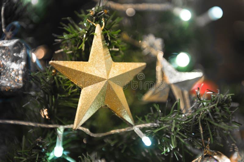 垂悬在美丽的Chrismas tr的圣诞节金黄光亮的星 库存图片
