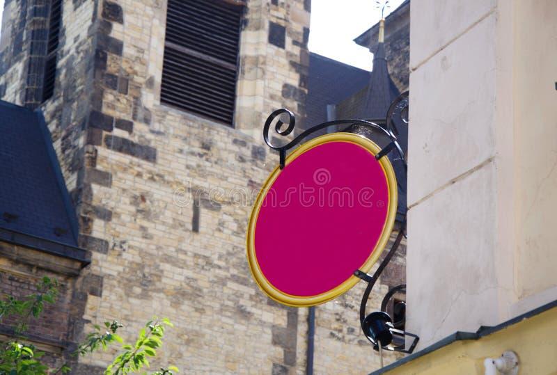 垂悬在老大厦的老桃红色房子标志 图库摄影