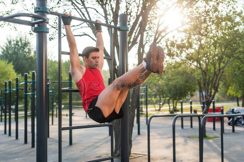 垂悬在肋木的Fitnes人执行腿上升 制定出吸收肌肉的核心交叉训练 库存图片