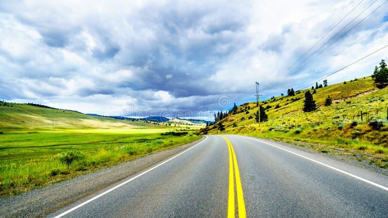 垂悬在肥沃的农地和绵延山的黑暗的云彩沿高速公路5A在Nicola湖附近,在坎卢普斯和梅里特之间 免版税库存照片