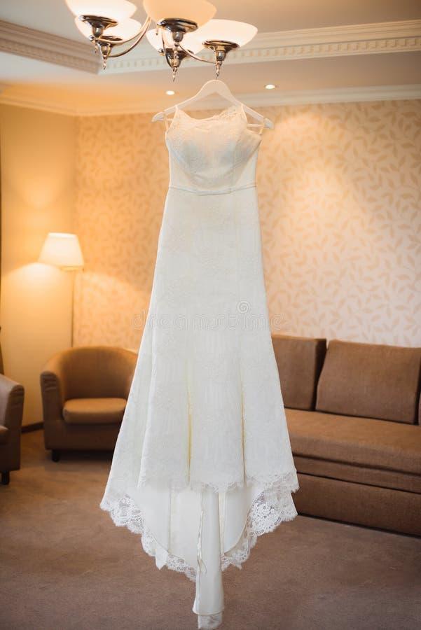 垂悬在色泽的婚礼礼服在室 库存图片