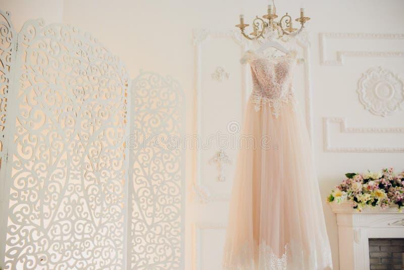 垂悬在色泽的婚礼礼服在旅馆客房 库存照片