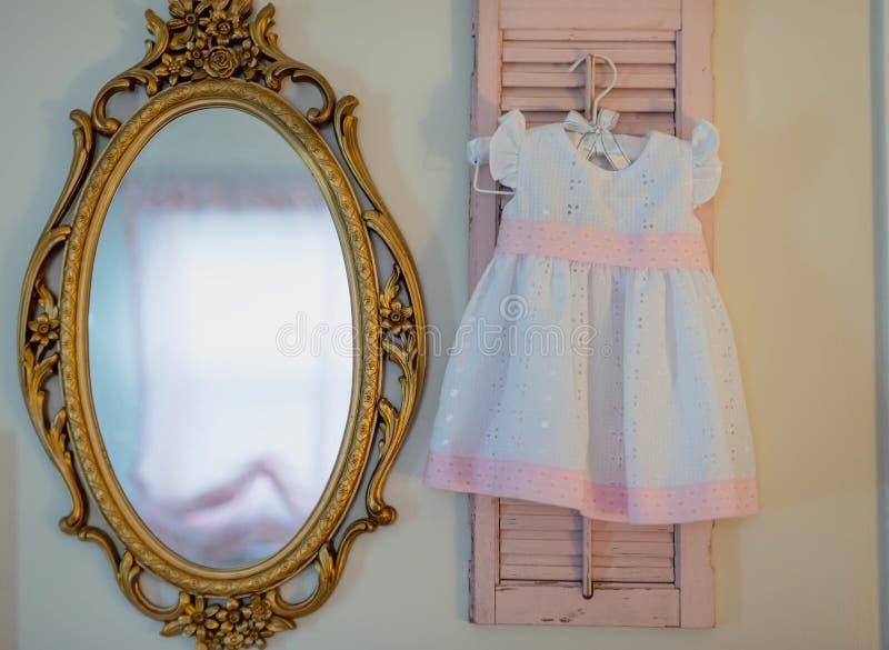 垂悬在葡萄酒桃红色快门的女婴的礼服 库存图片