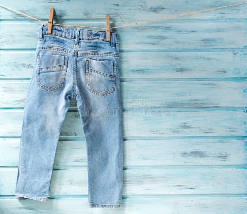 垂悬在蓝色木背景的晒衣绳的男婴蓝色牛仔裤 库存照片
