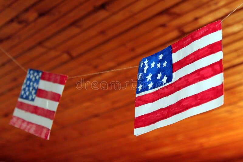垂悬在螺纹的美国国旗以木天花板为背景 库存图片