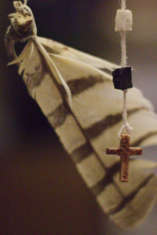 垂悬在螺纹的羽毛和十字架 免版税库存图片