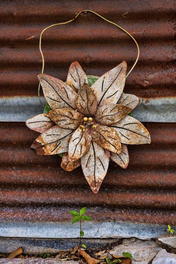 垂悬在被镀锌的金属墙壁上的生锈的老金属花 免版税图库摄影