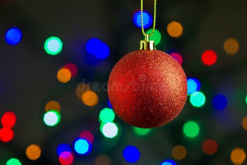 垂悬在金丝带的红色圣诞节球有五颜六色的bokeh背景 免版税库存图片