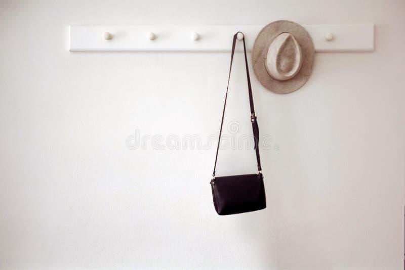垂悬在钉的帽子和袋子 免版税库存照片