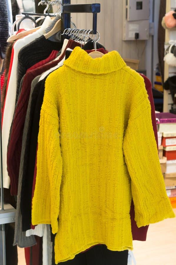 垂悬在销售中的妇女的五颜六色的外套 库存照片
