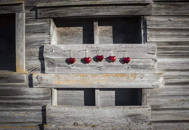垂悬在非常老木背景的一点红色心脏行  免版税库存图片