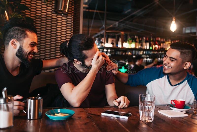 垂悬在顶楼咖啡馆的愉快的阿拉伯年轻人 小组混合的族种人获得乐趣在休息室酒吧 库存照片
