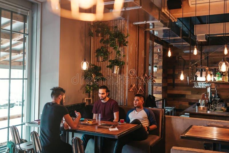 垂悬在顶楼咖啡馆的阿拉伯年轻人 小组有混合的族种的人谈话在休息室禁止和饮料 库存图片
