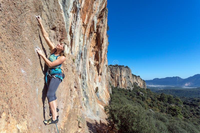 垂悬在高垂直的岩石的女性极端登山人 免版税库存照片