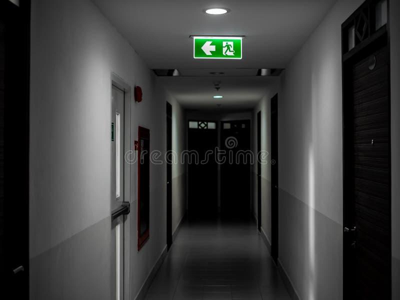 垂悬在黑暗的神奇走廊的天花板的绿色出口火标志在大厦在太平门门附近 图库摄影