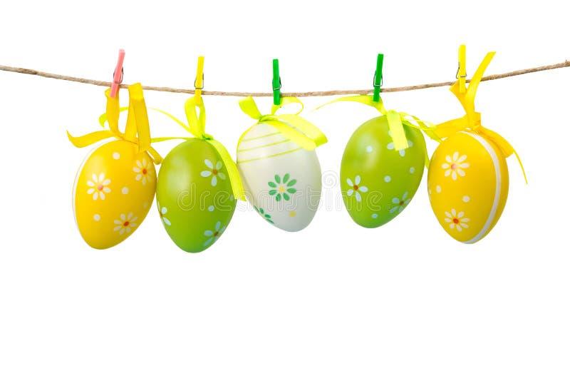 垂悬在绳索的五颜六色的复活节彩蛋,隔绝在白色背景 免版税库存图片