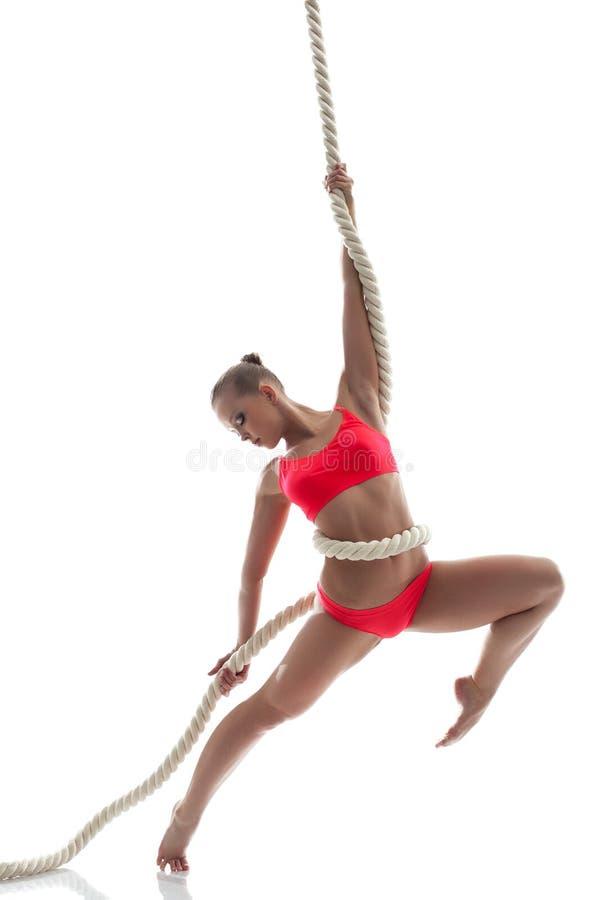 垂悬在绳索的优美的妇女在演播室 库存图片