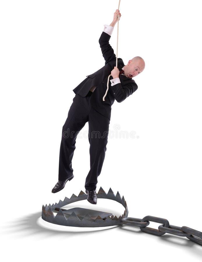 垂悬在绳索的商人 免版税库存照片