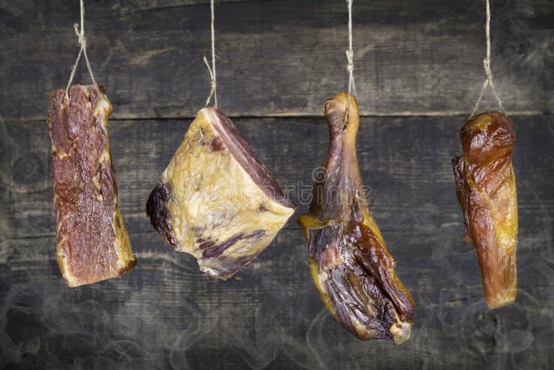 垂悬在绳索的熏制的肉反对与烟的木背景 免版税库存照片