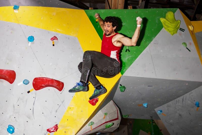 垂悬在bouldering的上升的墙壁上的攀岩运动员人,里面在色的勾子 图库摄影