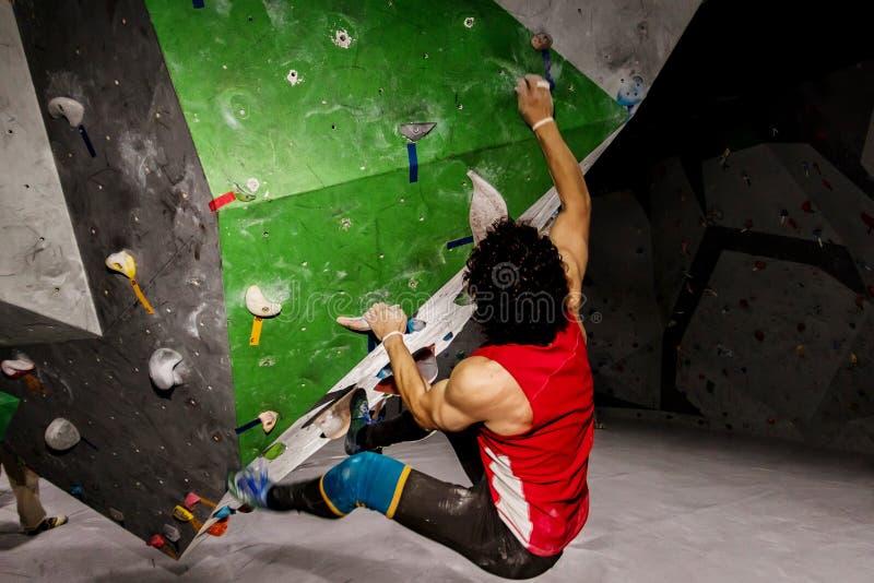 垂悬在bouldering的上升的墙壁上的攀岩运动员人,里面在色的勾子 免版税库存图片