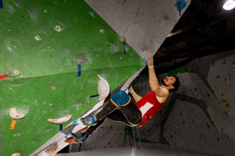 垂悬在bouldering的上升的墙壁上的攀岩运动员人,里面在色的勾子 库存照片