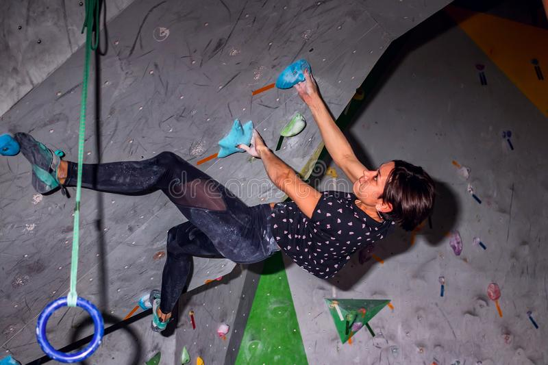 垂悬在bouldering的上升的墙壁上的攀岩运动员妇女,里面在色的勾子 库存照片