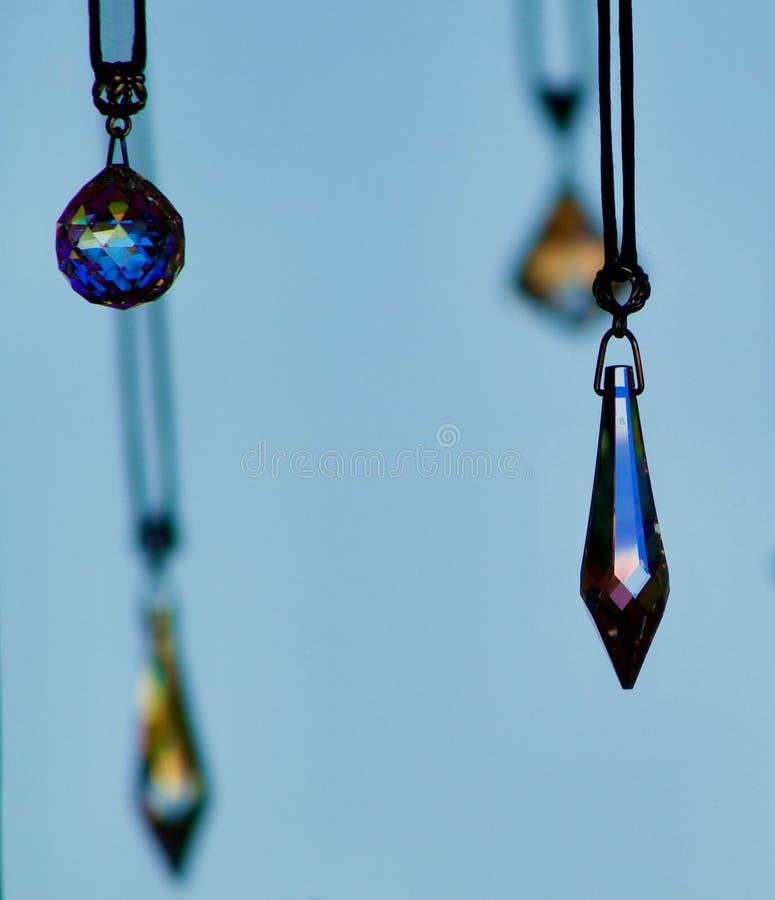 垂悬有蓝色背景的水晶pendents 免版税库存照片