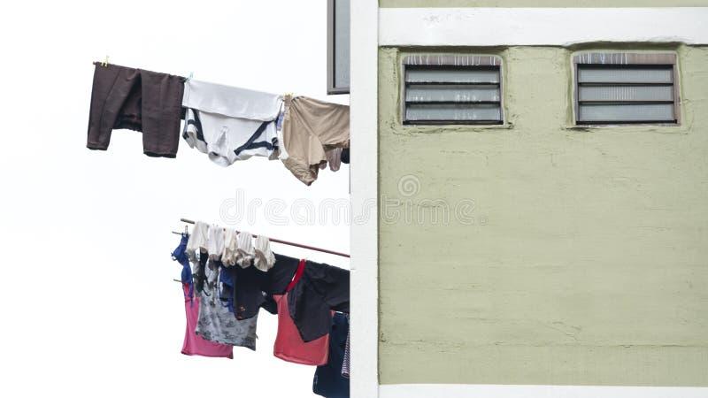 垂悬烘干在窗口大厦的洗衣店衣裳 免版税库存图片