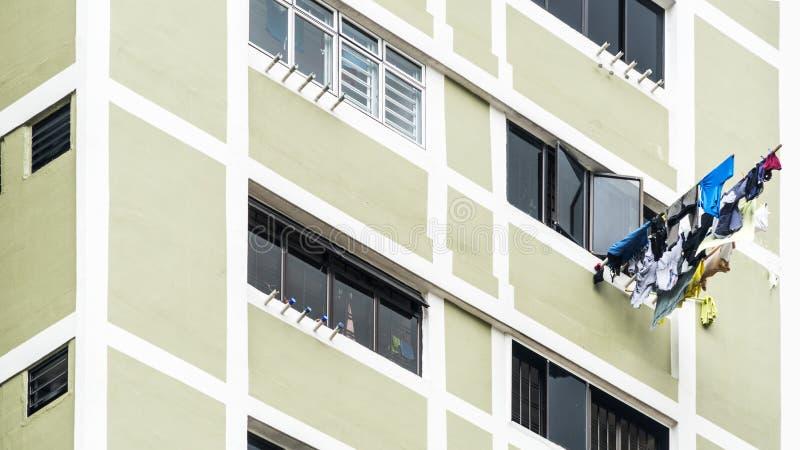 垂悬烘干在窗口大厦的洗衣店衣裳 库存照片
