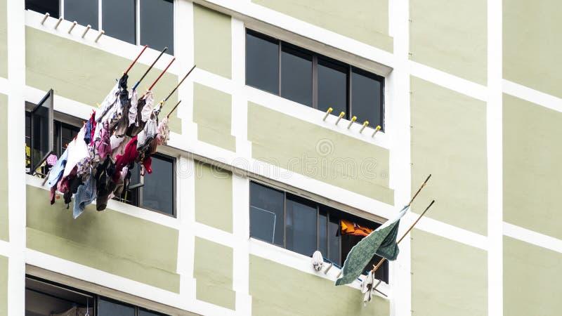 垂悬烘干在窗口大厦的洗衣店衣裳 免版税库存照片