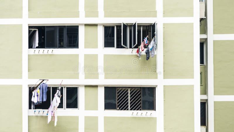 垂悬烘干在窗口大厦的洗衣店衣裳 免版税图库摄影