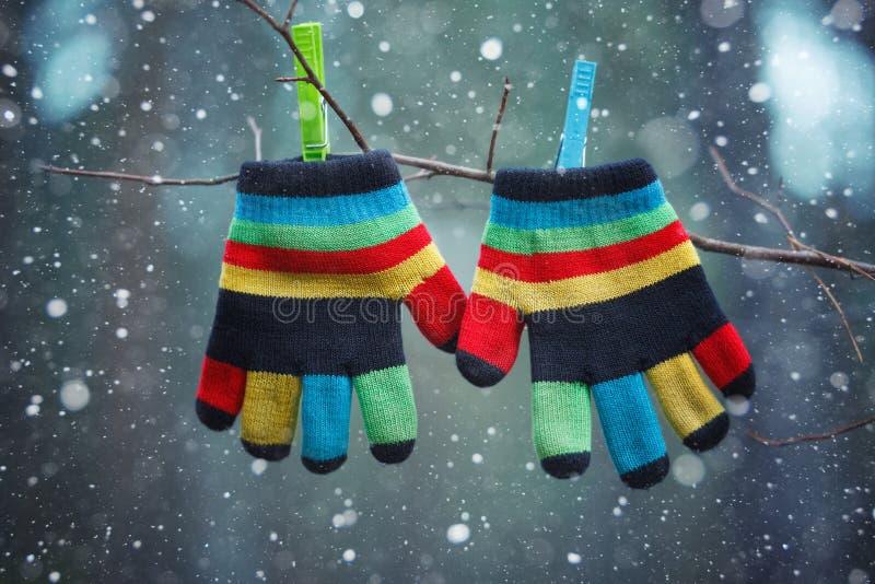 垂悬由一条螺纹的小的婴孩手套在冬日在落的雪下 免版税库存照片