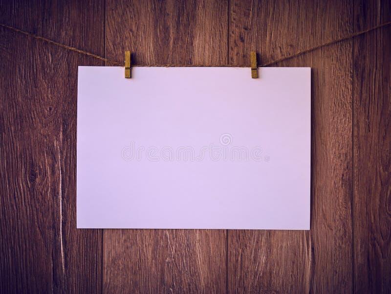 垂悬由在古色古香的土气木背景空的纸的绳索的空白的标志与拷贝空间 图库摄影