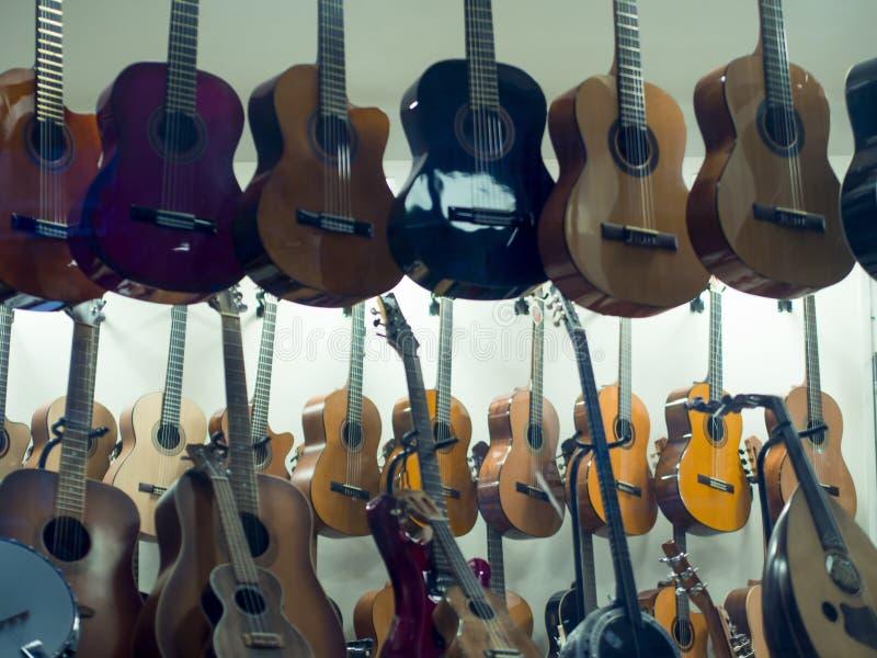 垂悬的吉他待售在音乐商店 免版税图库摄影