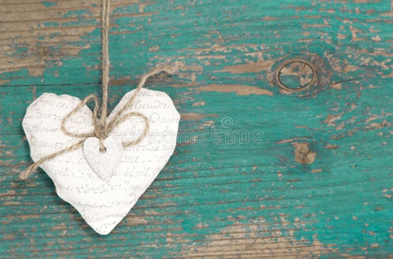 垂悬的心脏和绿松石木背景在乡村模式。 免版税图库摄影