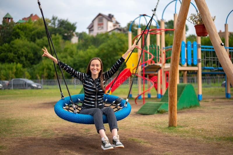 垂悬的摇摆的年轻愉快的妇女在公园微笑的手上,自由,周末,童年的概念 免版税库存图片