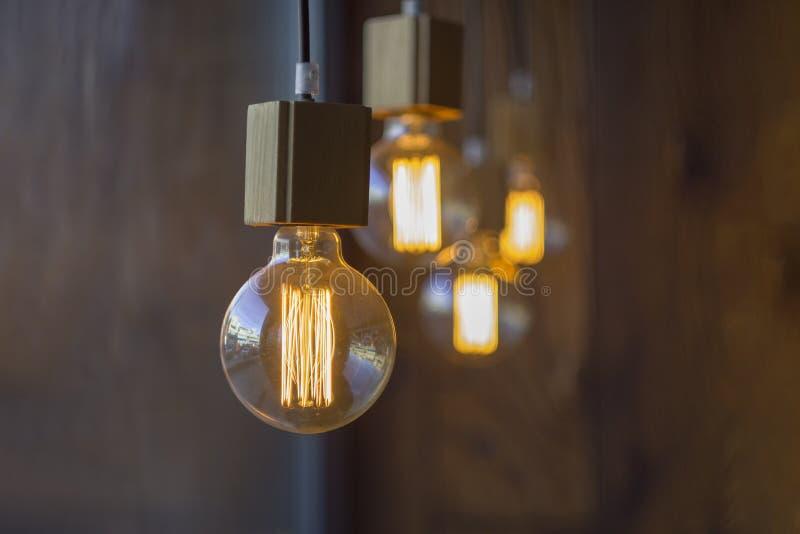 垂悬的球状减速火箭的葡萄酒爱迪生白炽电灯泡对有木纹理的被弄脏的棕色墙壁 免版税库存照片