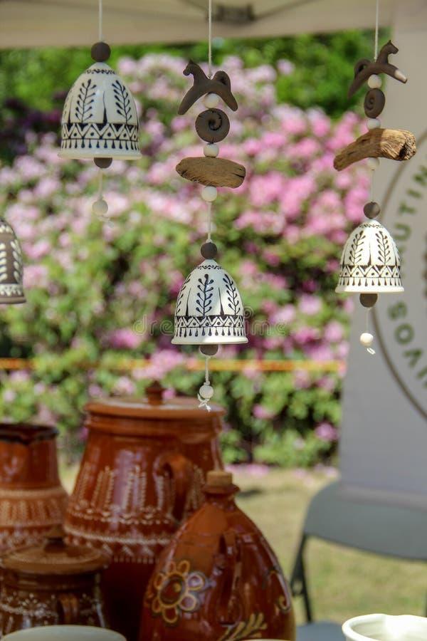 垂悬的精美手工制造陶瓷响铃和有些罐在背景中 免版税库存图片