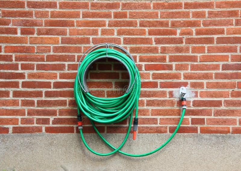垂悬红砖墙壁的绿色水水管 免版税图库摄影